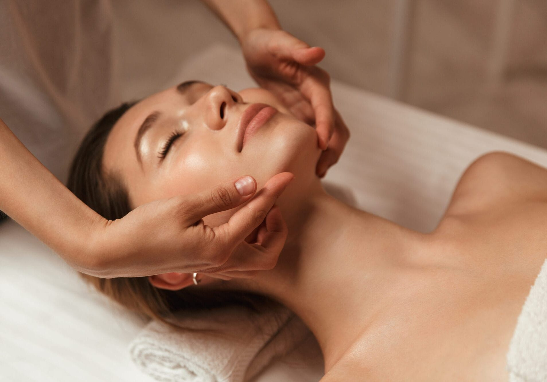 Young woman getting spa treatment with head massage at a spa center